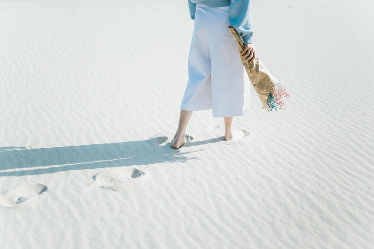 Low Section Of Woman Holding Flower Bouquet While Walking At Sandy Beach