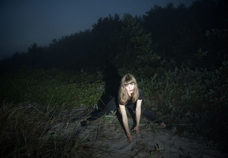 Full length portrait of woman stretching in forest at night