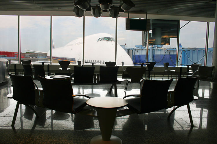 Jumbo Jet in front of waiting area in a airport terminal Plant Absence Aircraft Airplane Airport Airport Terminal Boeing 747 Business Cafe Cafeteria Chair Day Empty Food And Drink Food And Drink Industry Furniture Glass Glass - Material Indoors  Jet Jumbo Jet Lounge Chair Nature No People Restaurant Seat Setting Silhuette Table Transparent Window