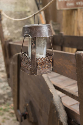 Close-up of electric lamp hanging on wood