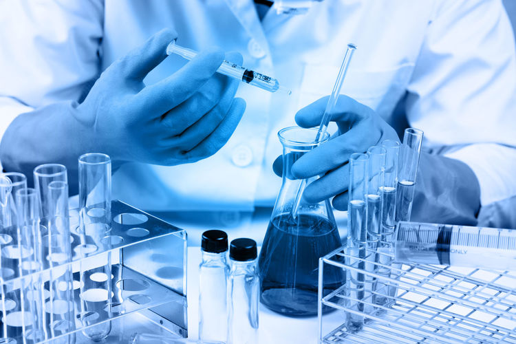 Midsection of scientist wearing gloves holding conical flask in laboratory