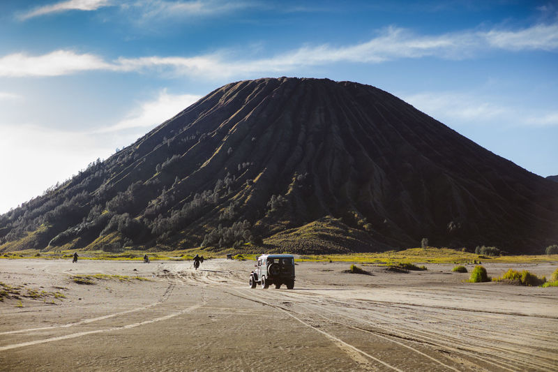 Off-Road Vehicle Driving And Riding Motorcycles By Volcano In Desert