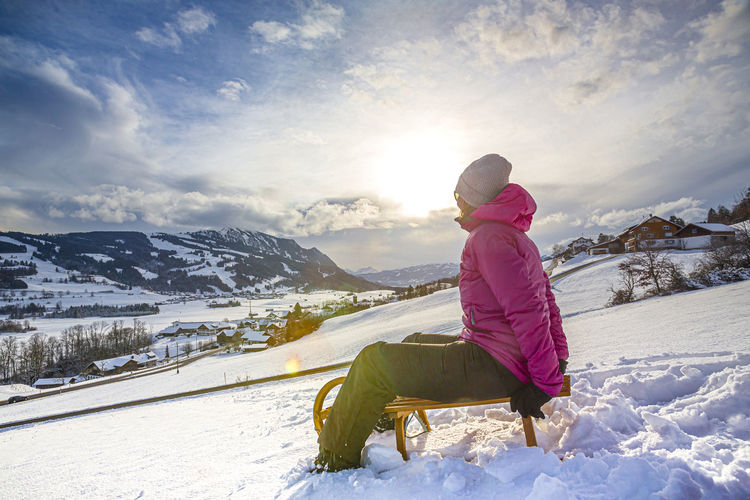 Woman on snowcapped mountains against sky during winter