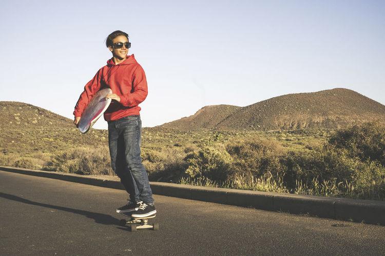 Smiling Teenage Boy Skateboarding On Road Against Clear Sky
