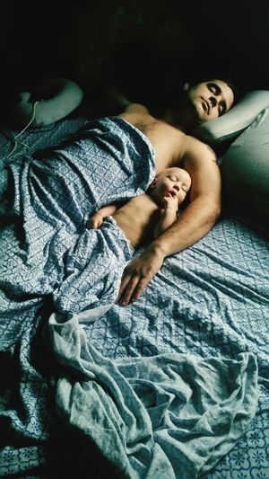 Father and son with blanket sleeping on bed at home