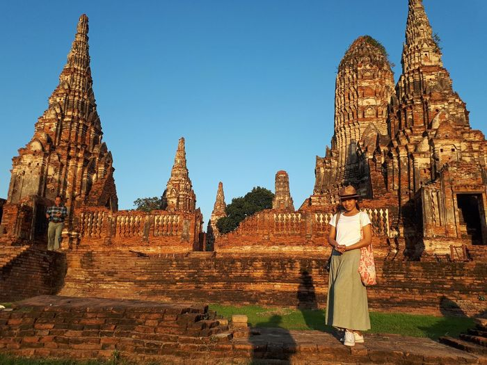 Portrait of woman standing at historic temple against clear blue sky