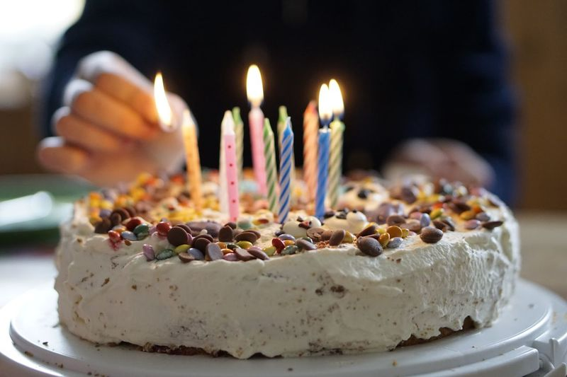 Midsection of person putting candles on birthday cake