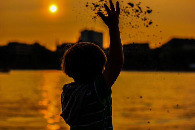 Rear view of boy looking at sea against sky during sunset