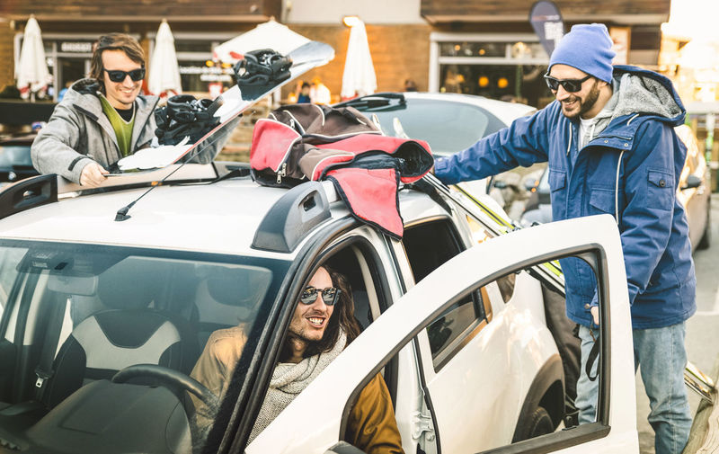 Happy Male Friends With Ski And Snowboard On Car