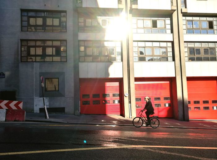 Urban Scene Sunny Day Red City Bicycle Sunlight Full Length City Life Architecture Building Exterior Built Structure Cycling Road Marking Shining Riding Moving Asphalt EyeEmNewHere