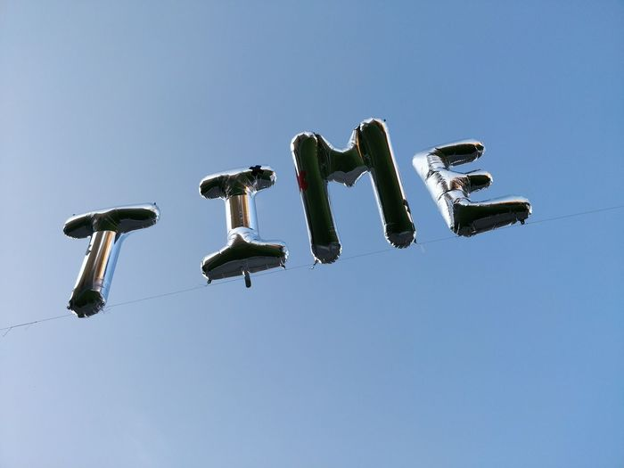 Helium ballons spell out time against blue sky