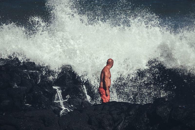 Shirtless Man Standing On Rock While Looking At Splashing Wave