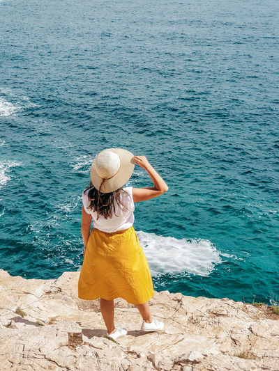 Young woman in yellow skirt standing on edge of cliff above sea.