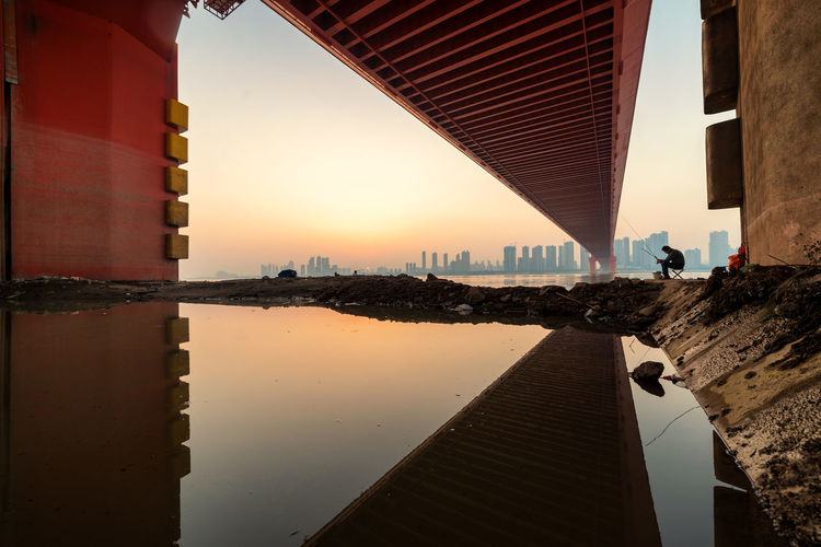 a triangular reflection. just arrived my hometown wuhan; there is a golden bridge too! The Color Of Business Dramatic Angles TakeoverContrast EyeEm Masterclass Eyeemphoto Landscape Sunshine Lifestyles Orange Color Outdoors Sunset Beauty People And Places Silhouette Architecture Architectural Feature Today's Hot Look Building Exterior Built Structure Cityscape City Battle Of The Cities Daily Commute