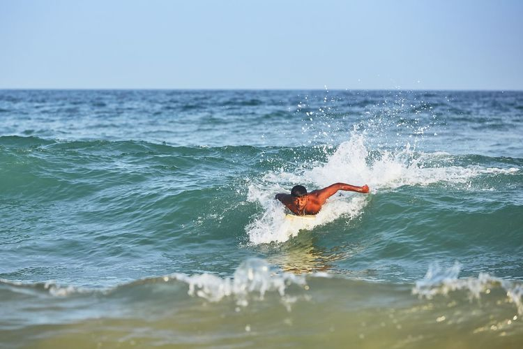 Man surfing on wave in sea against sky