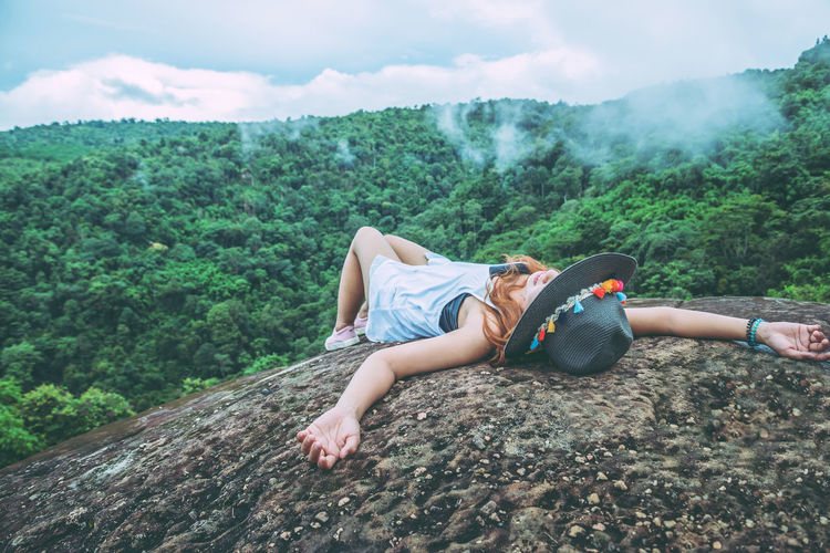 Young woman wearing hat lying on rock against sky