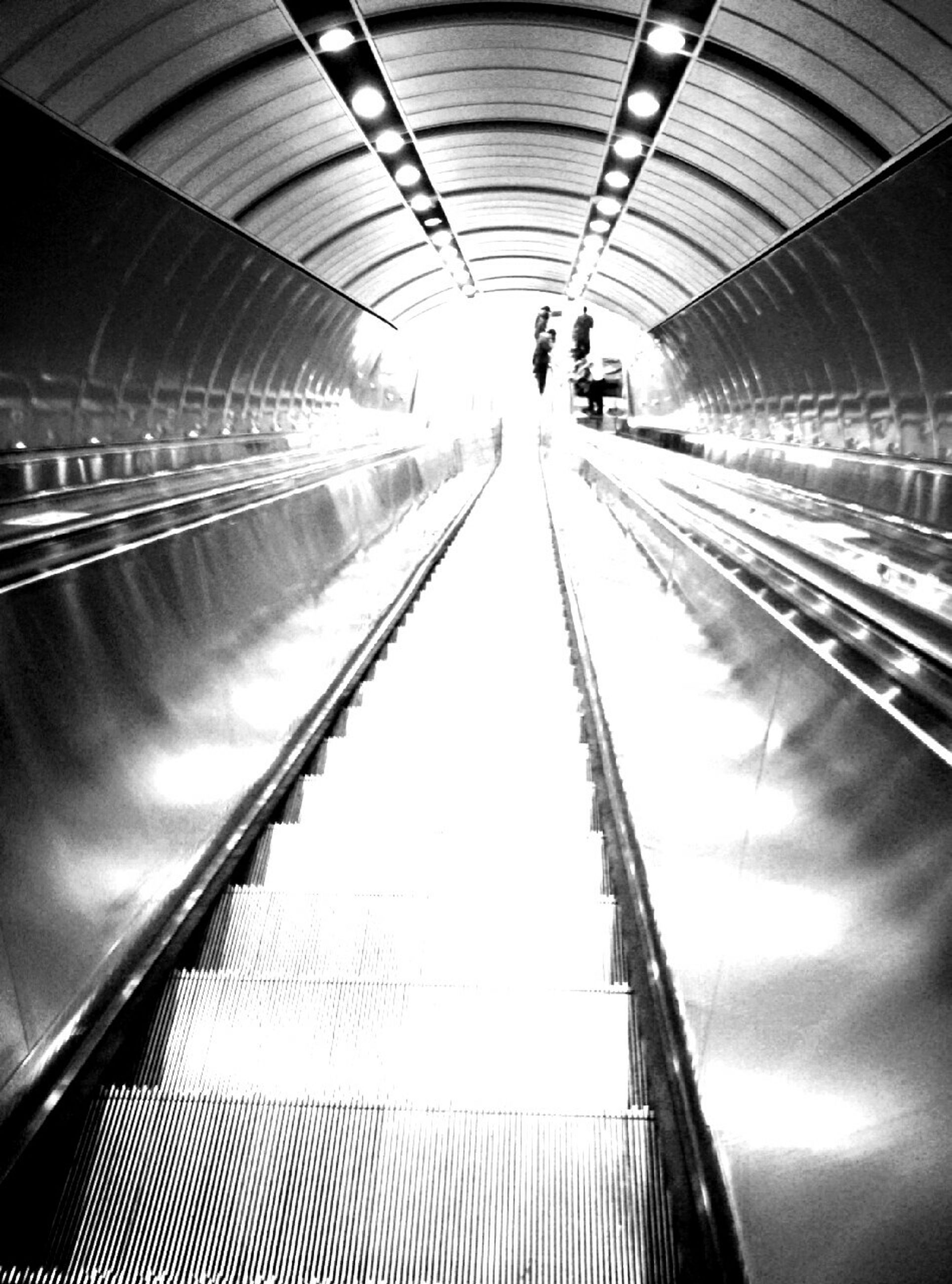indoors, transportation, railroad station, rail transportation, railroad track, public transportation, railroad station platform, escalator, subway station, ceiling, modern, illuminated, subway, diminishing perspective, the way forward, built structure, architecture, travel, incidental people, convenience