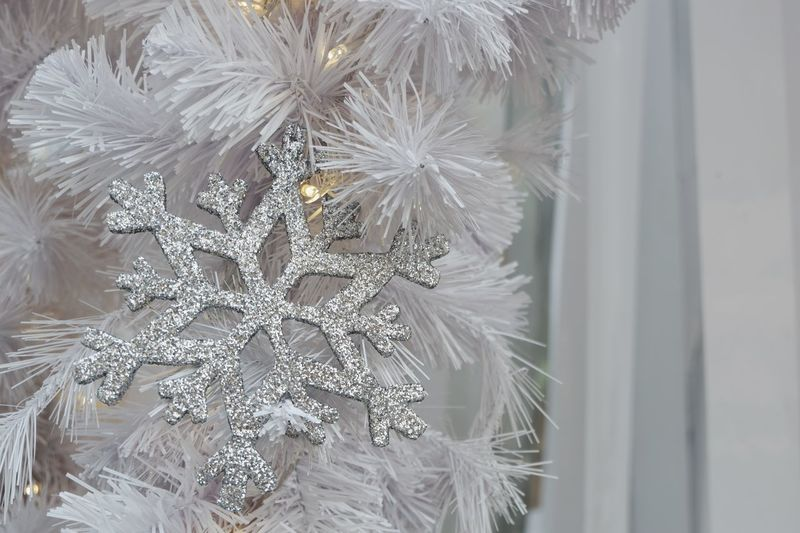 Sparkling silver snowflake with yellow light hangs from Christmas tree for background Holiday Decoration Snowflake Christmas Decoration Christmas Backgrounds White Silver  New Year Holiday Winter Frost Sparkle Celebration Close-up Celebration Event Christmas Indoors  Christmas Decoration Fragility No People Christmas Ornament Snowflake