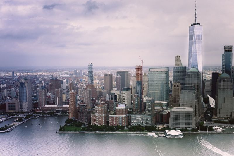 One world trade center by hudson river against cloudy sky