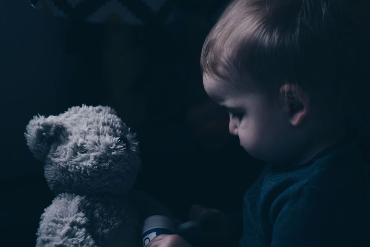Close-up of toddler playing with teddy bear in darkroom