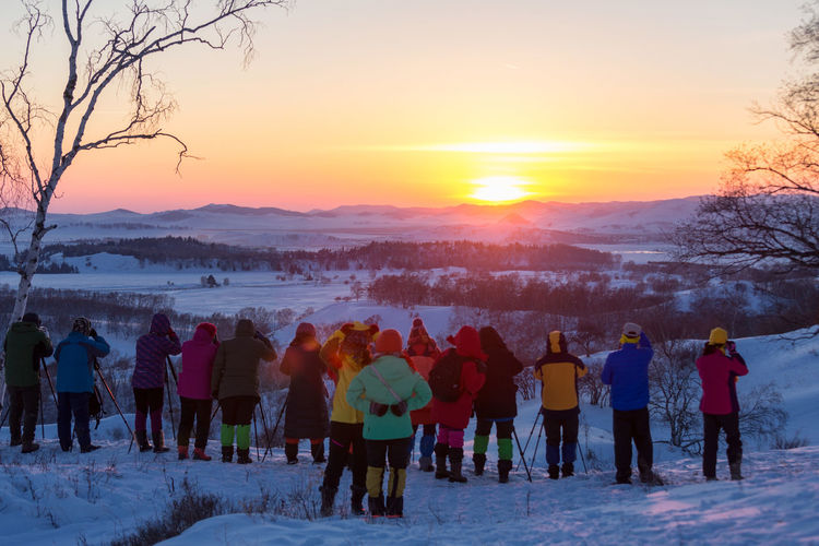 Group of people on snow covered land during sunset