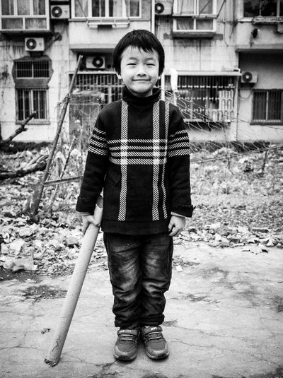 Portrait of boy standing against building