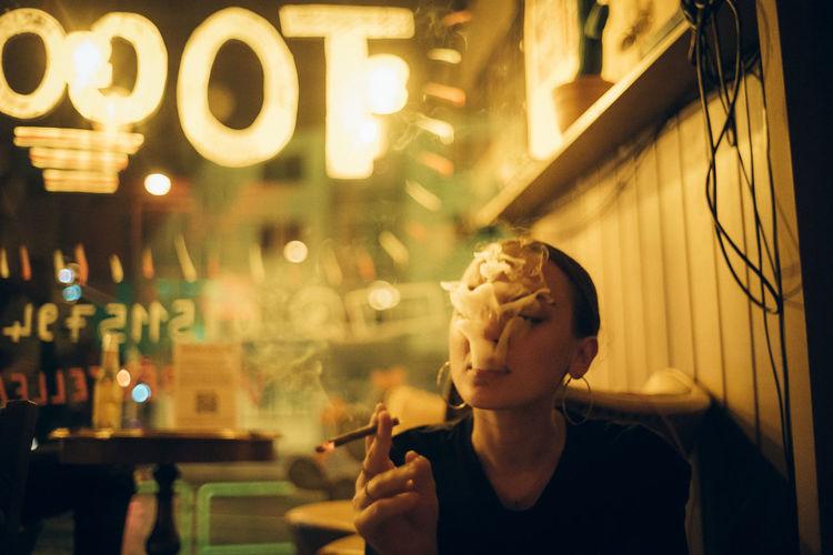 Portrait of man smoking cigarette at night