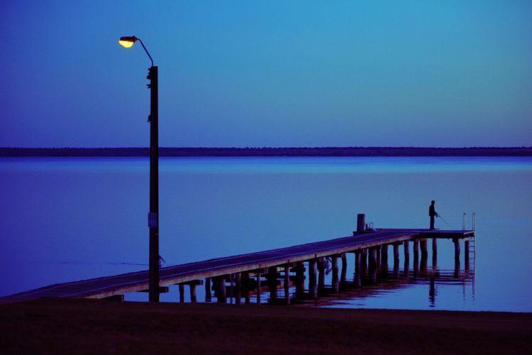 Pier on sea against clear sky at dusk