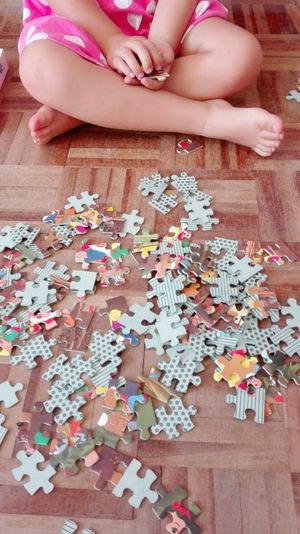 Low Section Of Child Playing With Jigsaw Puzzle