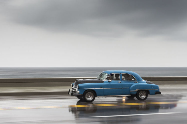 Car on road against sea and cloudy sky