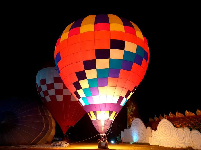 Low angle view of hot air balloons at night