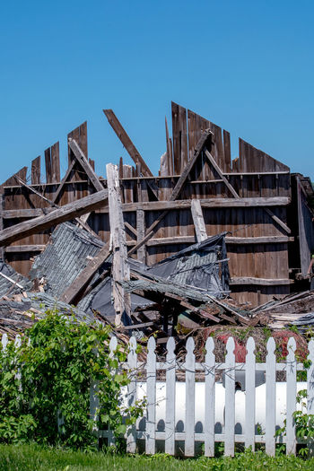 a ruined barn is a pile of rubble after strong storms, but a single wall and a picket fence still stands Barn Rural Architecture Blue Boundary Building Building Exterior Built Structure Clear Sky Countryside Damaged Day Destroyed Disaster Fence Low Angle View Nature One Wall Standing Outdoors Plant Roof Sky Storm Damage Strong Storms Tree