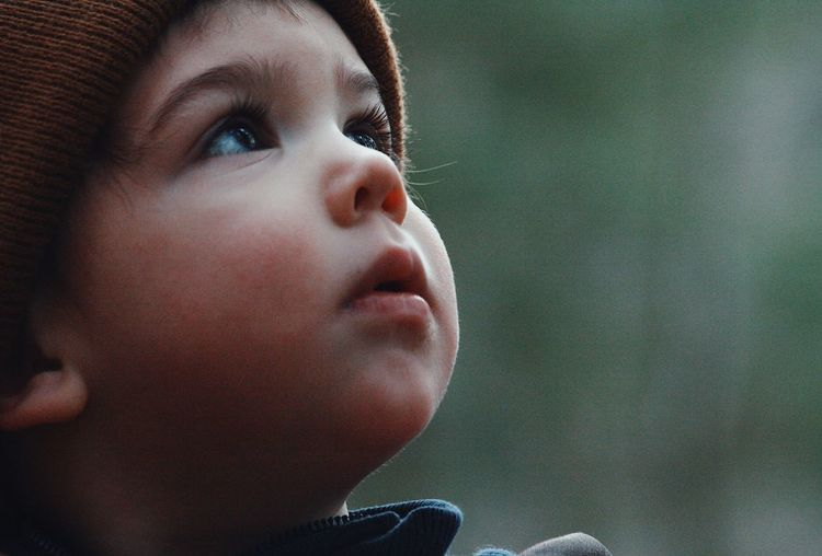 Close-up of cute thoughtful boy looking up