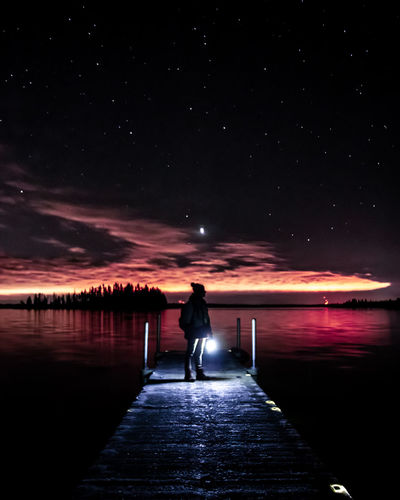 Silhouette man standing on illuminated pier over lake against star field