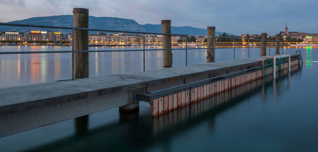 Pier over lake in city at dusk