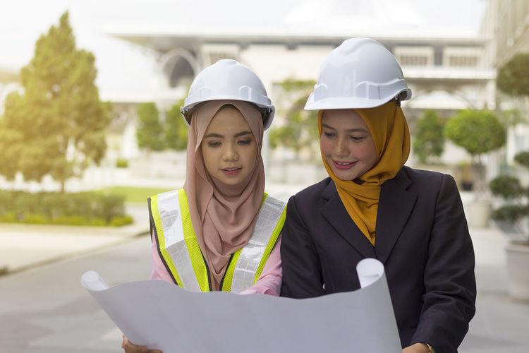 Female architects examining blueprint on street