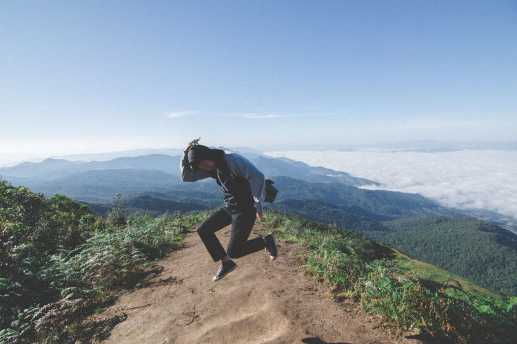 Man jumping over mountain against sky