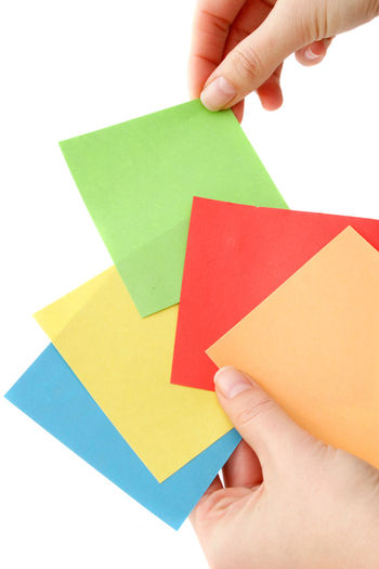 Cropped hand of person holding multi colored papers against white background