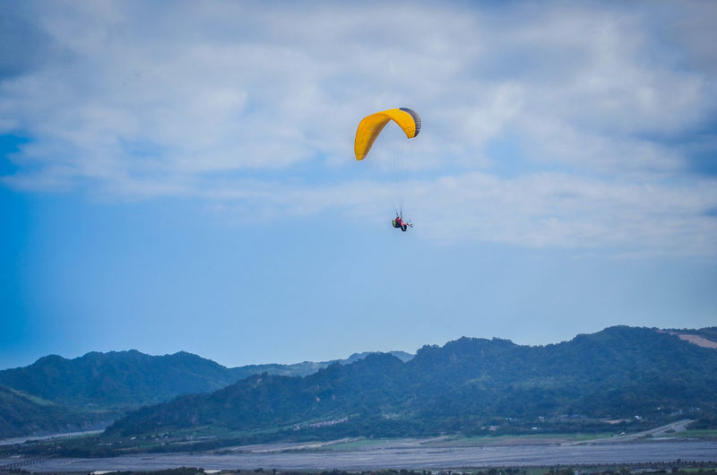 Person paragliding over sea against mountains
