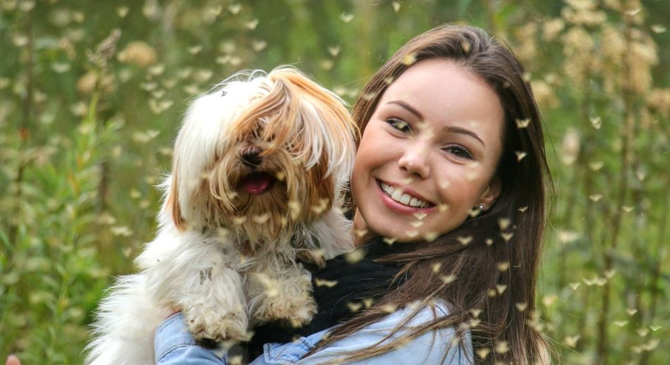 Portrait of smiling young woman holding dog