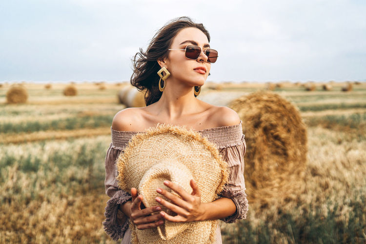 Smiling woman in sunglasses with bare shoulders on a background of wheat field and bales of hay.