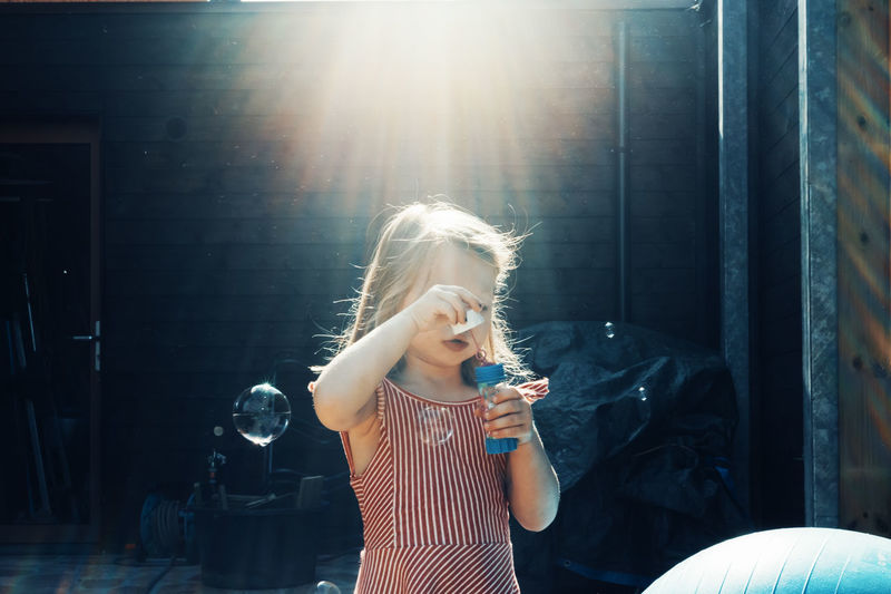 Girl holding bubble wand during sunny day