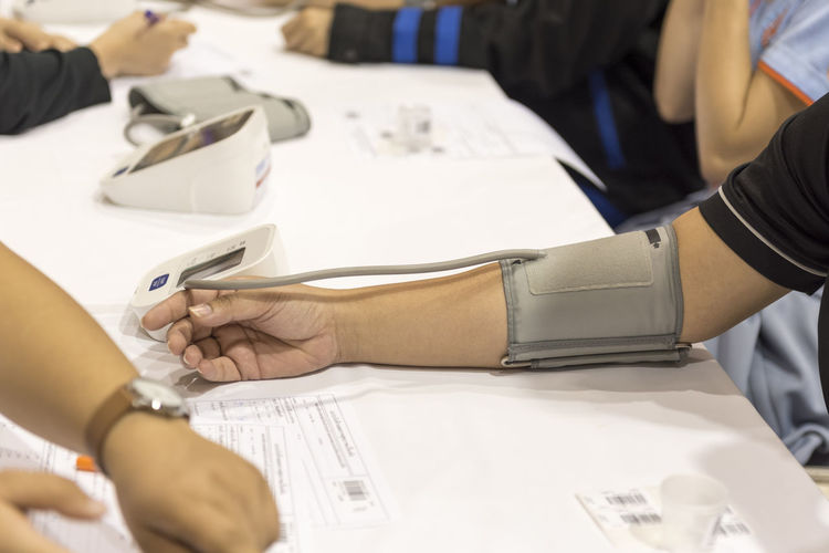 Cropped hand of patient with blood pressure gauge on table