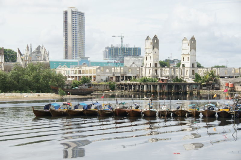Boats moored in river against buildings in city
