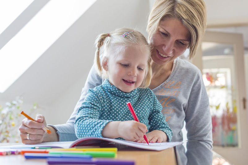 Mother Assisting Daughter In Coloring Book At Home