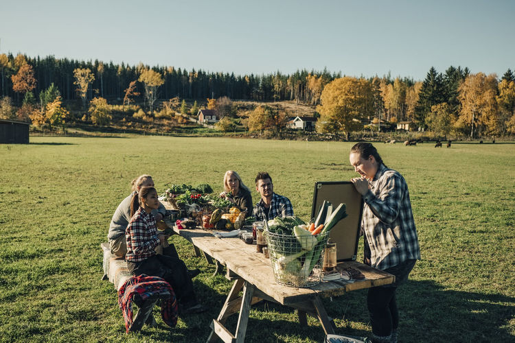 People sitting on table by field against trees