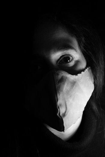 Close-up portrait of woman covering face in darkroom