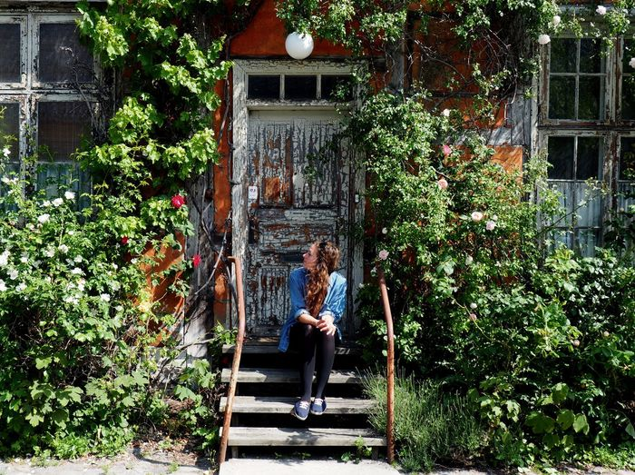 Young woman sitting on front stoop amidst plants