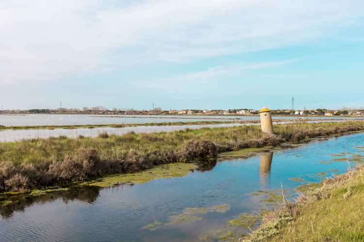 Italy, Cervia. This city is famous for its salt. Saltern date back to ancient times. Architecture Beauty In Nature Building Exterior Built Structure Cloud - Sky Day Environment Grass Lake Nature No People Outdoors Plant Reflection Scenics - Nature Sky Tower Tranquil Scene Tranquility Water