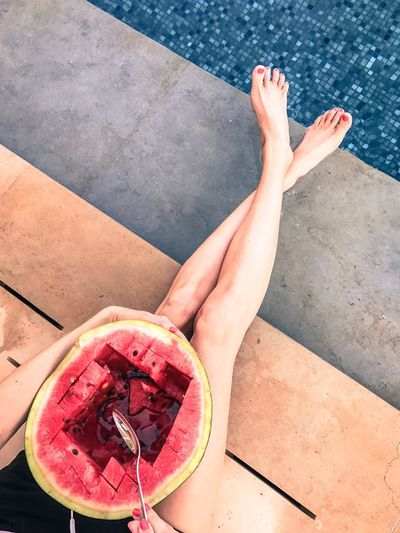 Low section of woman having watermelon while sitting at poolside